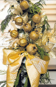 In keeping with the warm metallic theme of the front door wreath, the newel post is decorated with gilded pomegranates, sprays of champagne and warm golden leaves.