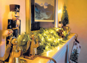 A long fir mantlepiece is laced with lights and pine cones and accessorized by Nutcracker figurines, brass candlesticks and antique brass stocking holders. A live topiary adds to the overall balanced look.